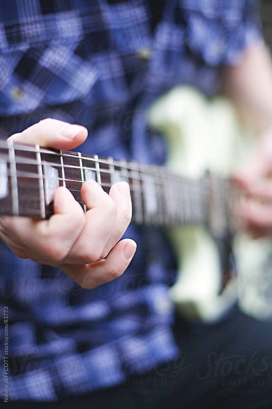 close up of hand playing guitar by Natalie JEFFCOTT for Stocksy United