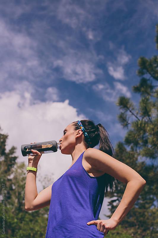 Women Drinking from a Water Bottle by Gabrielle Lutze for Stocksy United