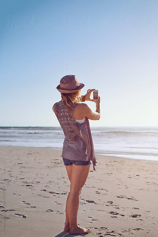 Beautiful Girl on the beach near sunset taking a photograph by Aila Images for Stocksy United