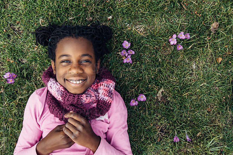 Smiling black girl on grass with crocus flowers by Gabriel (Gabi) Bucataru for Stocksy United