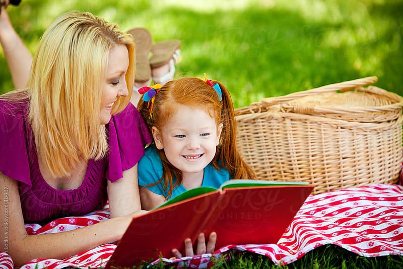 Park: Mom Helps Girl Read Storybook by Sean Locke for Stocksy United