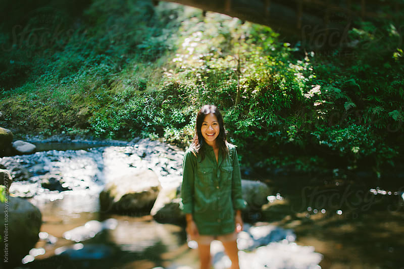 Woman smiling surrounded by beautiful forest and water by Kristine Weilert for Stocksy United