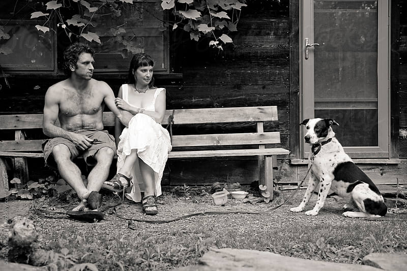 Hippy Couple sitting on bench with dog by Sari Wynne Ruff for Stocksy United