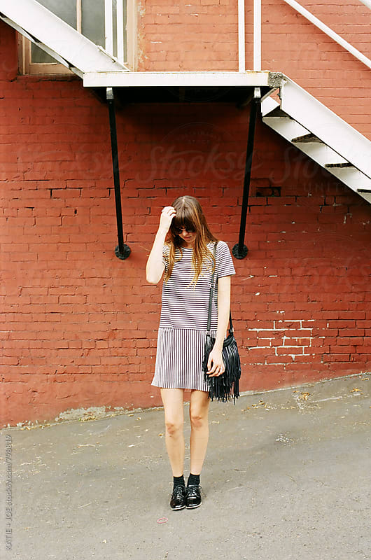 girl with bangs in a striped dress and sunglasses standing by a fire escape and a red building by KATIE + JOE for Stocksy United