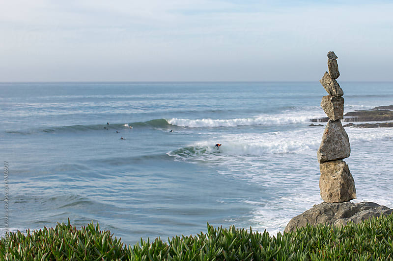 Stacked rocks at the beach with surfers in the distance by Carolyn Lagattuta for Stocksy United
