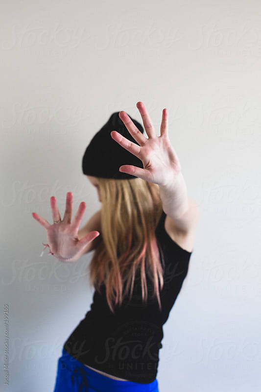 Assertive teen looks away from camera and puts her hands in front of her face as if to say 'stop' by Jacqui Miller for Stocksy United