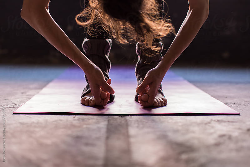 Closeup of a yoga practitioner's feet and hands during yoga exercize  by Jovo Jovanovic for Stocksy United