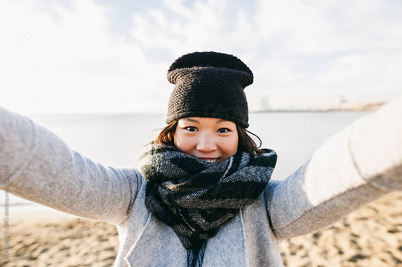Portrait of a chinese woman taking a selfie on the beach on winter. by BONNINSTUDIO for Stocksy United