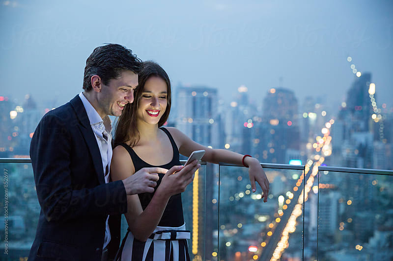 Handsome young couple looking at a smartphone together  by Jovo Jovanovic for Stocksy United