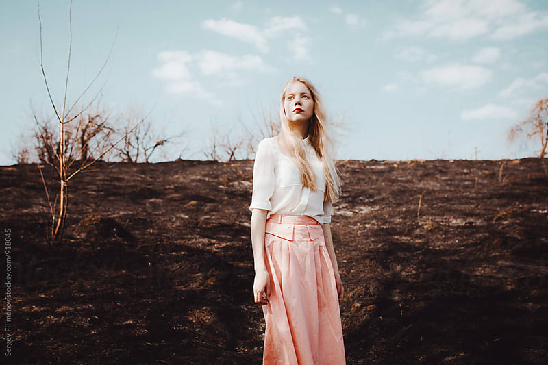 Young blonde woman stay is burned field white shirt and pink skirt by Sergey Filimonov for Stocksy United