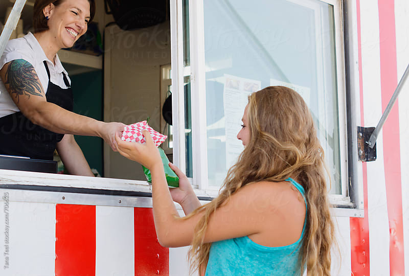 Smiling food vendor hands food to waiting customer by Tana Teel for Stocksy United