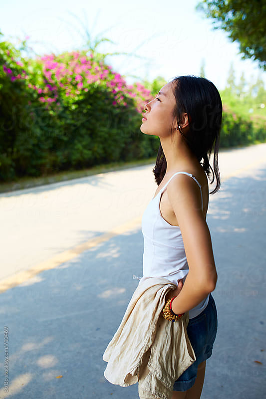 young asian woman standing outdoor by the road by Bo Bo for Stocksy United