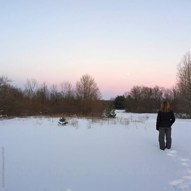 A Girl Standing In Fresh Snow Durning A Winter Sunset With A Tiny Full Moon by ALICIA BOCK for Stocksy United