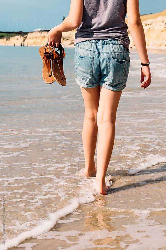 teenager walking barefoot along the beach in South Australia by Gillian Vann for Stocksy United
