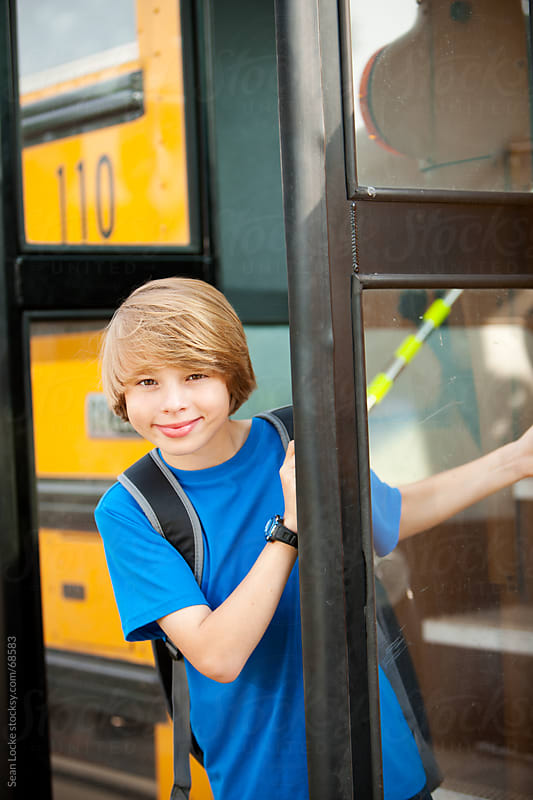 School Bus: Kid Peeks Around Bus Door by Sean Locke for Stocksy United