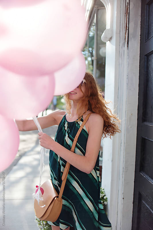A teenage girl holding balloons walking down a city street by Chelsea Victoria for Stocksy United
