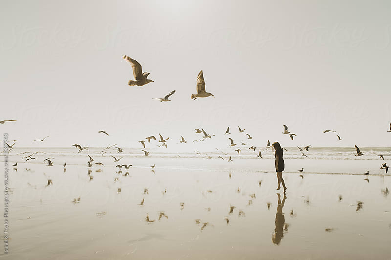 Girl walking with Seagulls  by Isaiah & Taylor Photography for Stocksy United