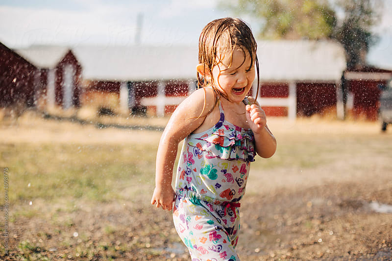 Wet toddler girl making a funny face while being sprayed with water. by Jessica Byrum for Stocksy United