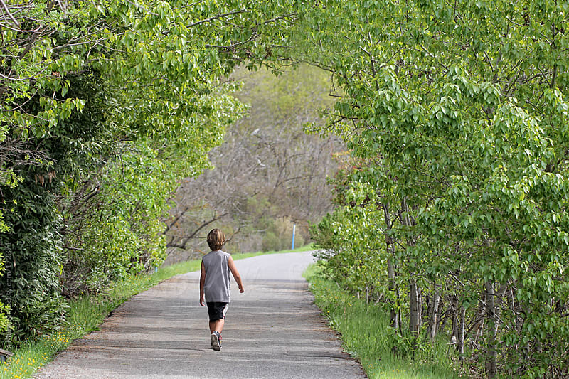 Young boy walks through tunnel of trees on nature path trail by Monica Murphy for Stocksy United
