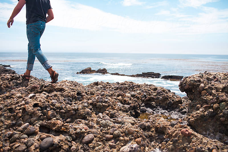 Man walking on rocks by Kayla Snell for Stocksy United