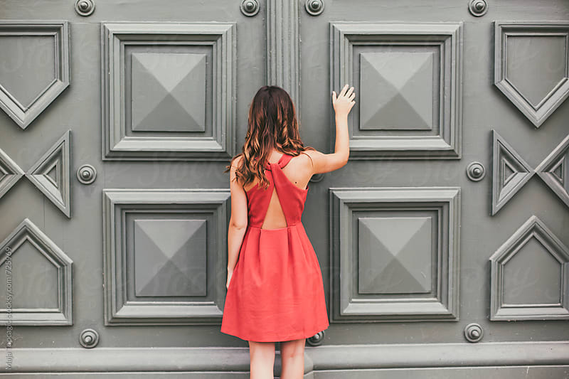 Beautiful brunette in an orange dress in front of an old doors by Maja Topcagic for Stocksy United