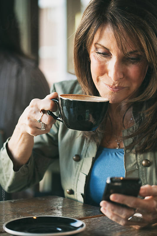 Cafe: Woman Drinks Coffee And Checks Text Messages by Sean Locke for Stocksy United