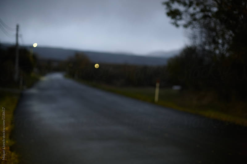 Blurry country road at twilight by Miquel Llonch for Stocksy United