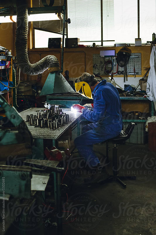 locksmith welding in his workshop by Leander Nardin for Stocksy United