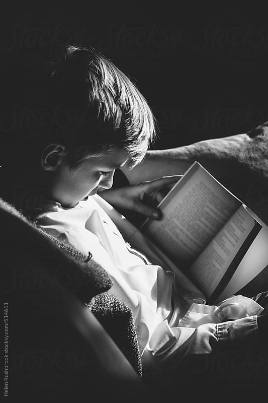 A black and white image of a pre-teen boy reading a book. by Helen Rushbrook for Stocksy United