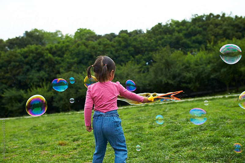 little asian girl playing soap bubble outdoor by Bo Bo for Stocksy United