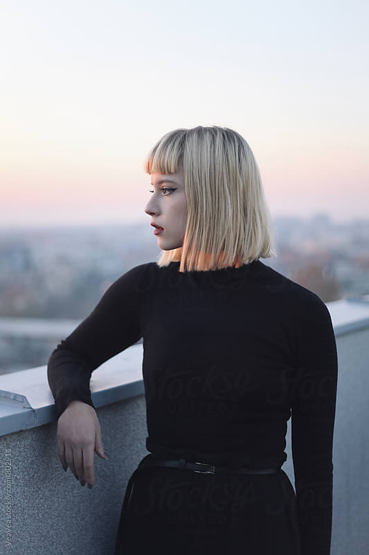 Young stylish woman on the roof of the building during sunset  by Marija Mandic for Stocksy United