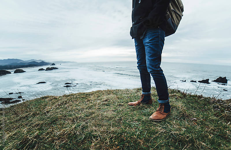 Man Standing on Hill Overlooking Ocean by Evan Dalen for Stocksy United