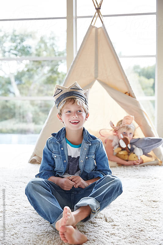 Portrait of little boy in front of teepee tent with sister in background by Trinette Reed for Stocksy United