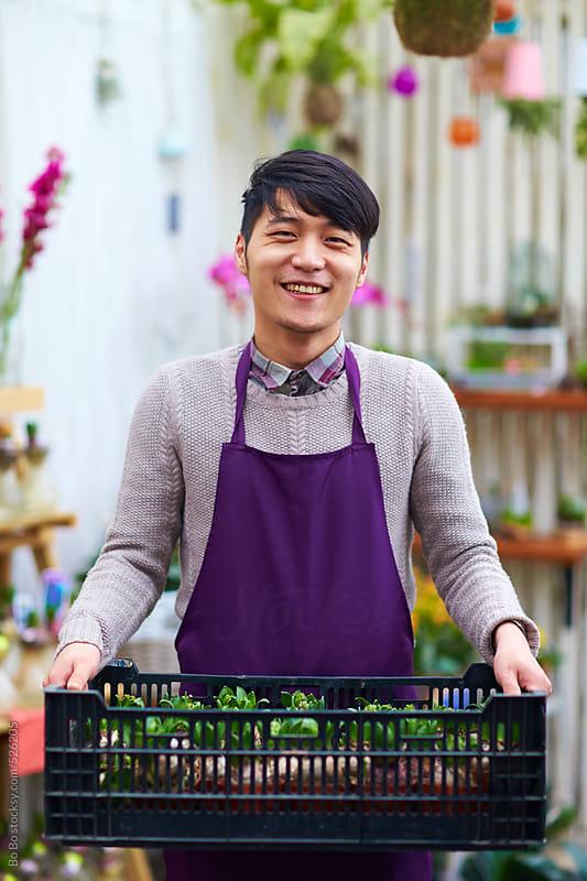 happy florist in shop by Bo Bo for Stocksy United