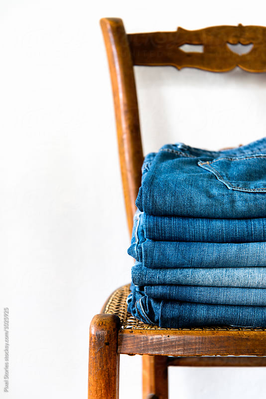 Folded jeans on wooden chair by Pixel Stories for Stocksy United
