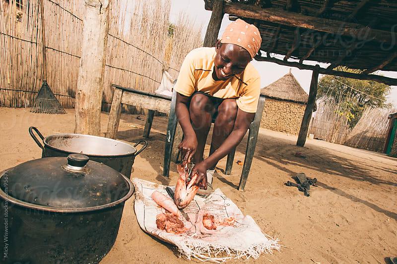 Namibian Hambukushu woman preparing fish  by Micky Wiswedel for Stocksy United