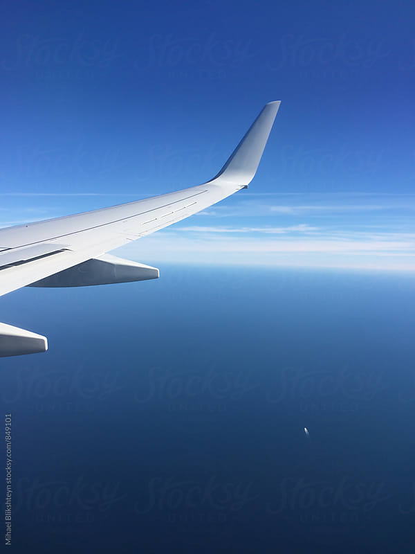 View of an airplane wing and blue sky with white clouds in the distance by Mihael Blikshteyn for Stocksy United