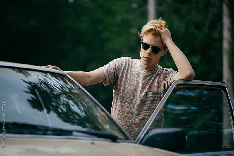 A young blonde man leaning against the open door of his car by Ania Boniecka for Stocksy United