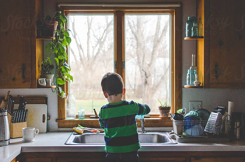 Boy standing at kitchen sink doing dishes by Lindsay Crandall for Stocksy United