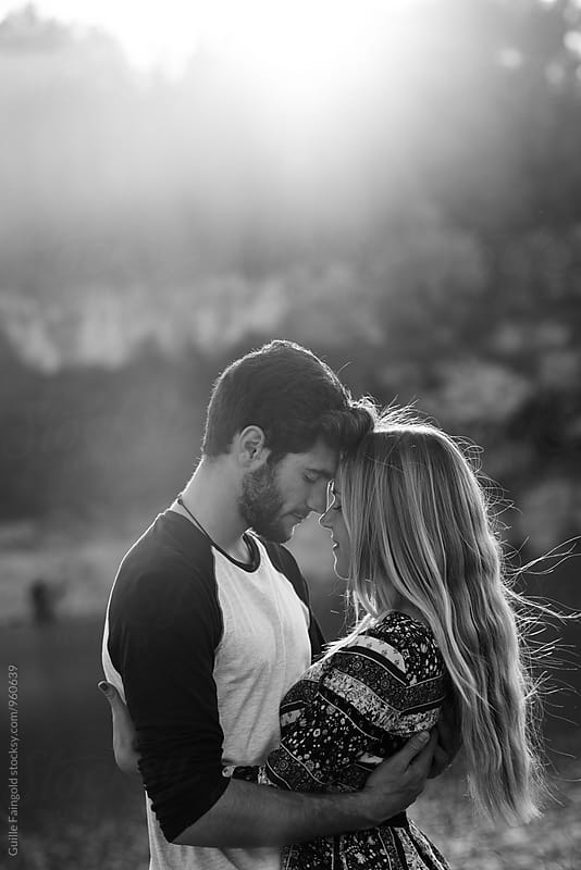 Side view of young couple hugging with eyes closed by Guille Faingold for Stocksy United