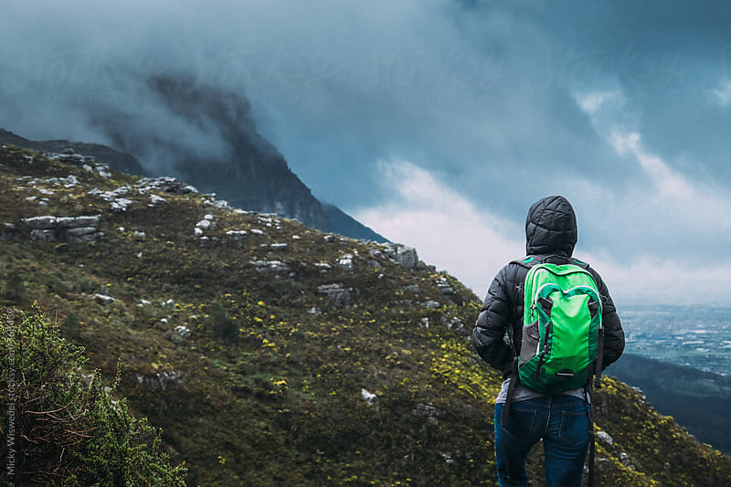 Hiker with a backpack on a mountainside in stormy weather by Micky Wiswedel for Stocksy United