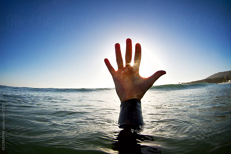 A hand reaching up out of the surface of the ocean in late afternoon light. by Robert Zaleski for Stocksy United
