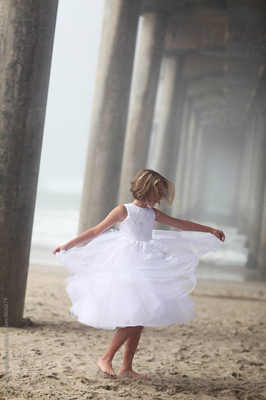 Girl in Formal White Dress Twirling On The Beach Under Pier by Dina Giangregorio for Stocksy United