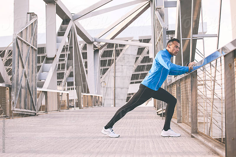 Sport man stretching on the urban background. Listening music to the smart phone. by BONNINSTUDIO for Stocksy United