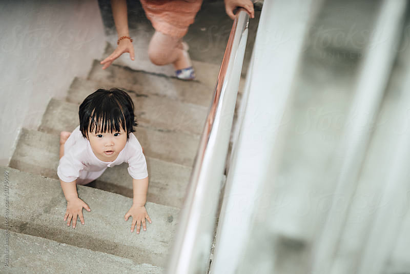 baby learning climb stairs by Pansfun Images for Stocksy United