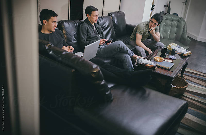 Group of Young Male University Students - Roommates Playing Video Game and Laptop on Couch by Joselito Briones for Stocksy United
