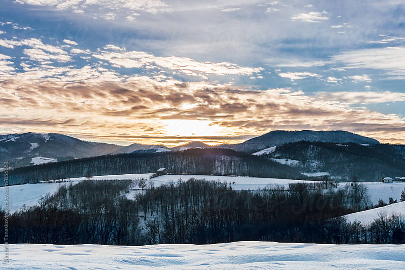 Beautiful sunset above the mountains and snow covered fields by Dimitrije Tanaskovic for Stocksy United