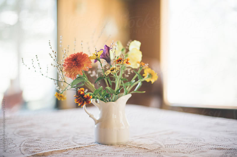 Bouquet of Wild Flowers in White Pitcher on White Lace Tablecloth by Briana Morrison for Stocksy United