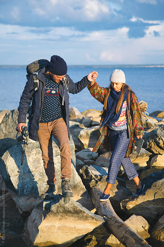 Couple walking on rocky shore with backpacks by Danil Nevsky for Stocksy United