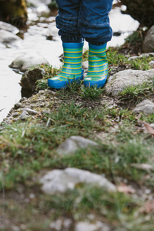 Kid's legs wearing blue jeans and rubber boots  by Amir Kaljikovic for Stocksy United